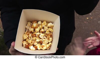 Family eating popcorn close up