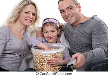 Family eating popcorn in front of television