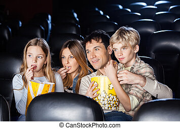 Family Eating Popcorn While Watching Film In Theater