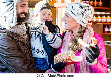 Family eating rolls and sausage on Christmas Market