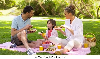 family eating sandwiches on picnic at summer park - family,...