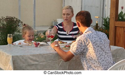 Family eating simple food at the dinner table in backyard area