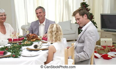 Family eating turkey at their Christmas Eve Dinner