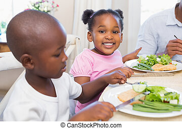 Family enjoying a healthy meal together with daughter smiling at