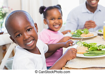 Family enjoying a healthy meal together with son smiling at came