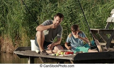 Family enjoying meal by the lake while fishing