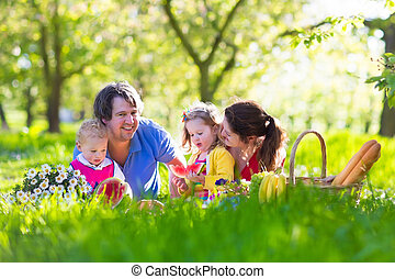 Family enjoying picnic in blooming garden - Family with ...
