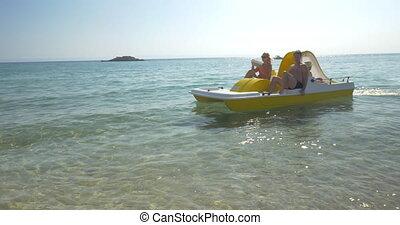 Family enjoying sea ride on pedal boat