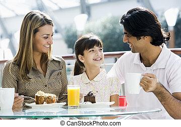 Family enjoying snack at cafe