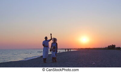Family enjoying summer vacation on sand beach flying kite at sunset