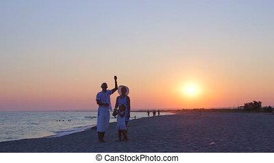 Family enjoying summer vacation on sand beach flying kite at sunset