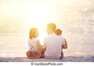 Family enjoying sunset view at beach