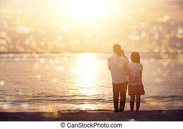 Family enjoying sunset view at coastline