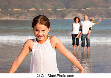 Family Enjoying the a stroll on the beach - Young Family...