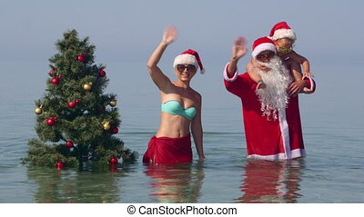Family enjoying tropical beach holiday near Christmas tree in water