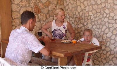 Family enjoying warm days in the outdoor kitchen beside summer house