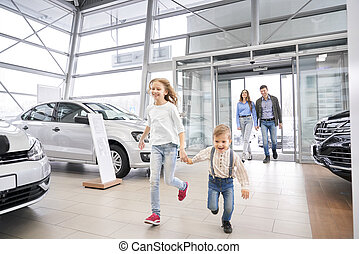 Family entering car dealership, happy children running.