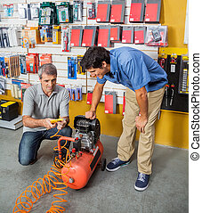 Family Examining Air Compressor In Store