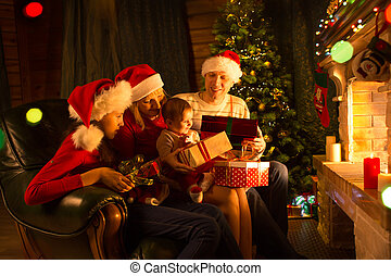 Family exchanging gifts in front of fireplace at Christmas...