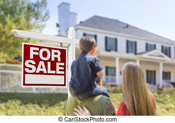Family Facing For Sale Real Estate Sign and House