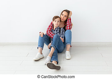 Family, fashion and mother day concept - teen boy hugging his mom on white background