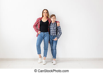 Family, fashion and mothers day concept - Portrait of mother and son dressed in plaid shirts on white background with copy space