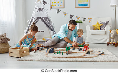family father and children play a toy railway in playroom - ...