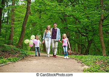 Family father and mother with two kids walking in summer green city park on picnic, happy holidays parents and children on nature