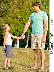 Family Father Man and Son Boy Child holding hand in hand Outdoor Happiness emotion with summer nature on background