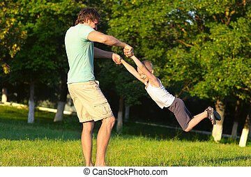 Family Father Man and Son Boy playing Outdoor park flying round Happiness emotion with summer nature on background