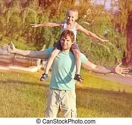 Family Father Man and Son Boy sitting on shoulders playing Outdoor park Happiness emotion with summer nature on background
