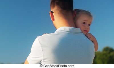 family, fatherhood and leisure concept - happy father holding his little daughter outdoors