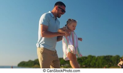 family, fatherhood and leisure concept - happy father playing with little daughter on beach