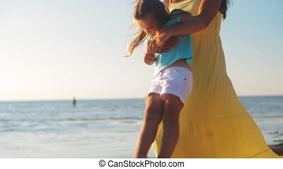 family, fatherhood and leisure concept - happy mother playing with little daughter on beach