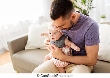 close up of father with little baby girl at home