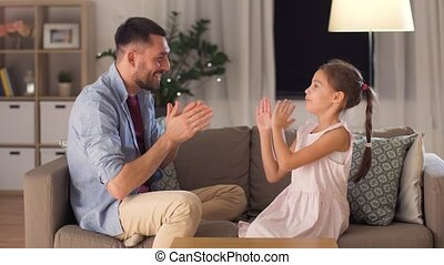 father and daughter playing clapping game at home - family,...