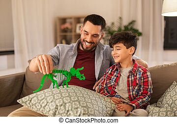 father and son playing with toy dinosaur at home