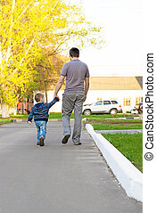 Family feet and legs in jeans. Father and son walking in an urban neighborhood.