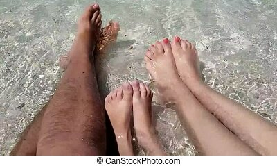 Family feet relaxing in the beach. Summer holidays, Vacation concept.