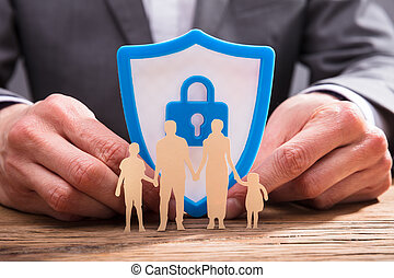 Family Figure Cutout On Wooden Desk