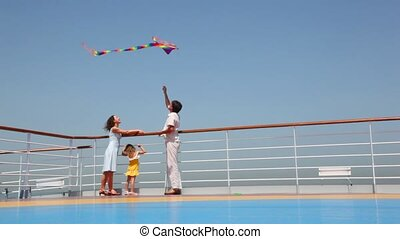 family flying a kite on deck of ship