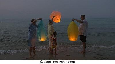 Family flying sky lantern on the beach