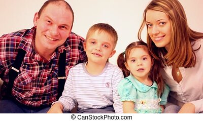 Family four with two children peer into camera and smile