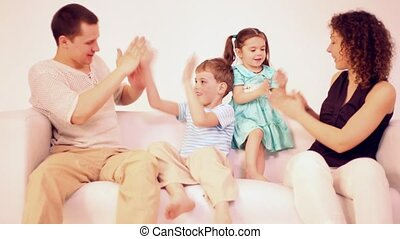 Family four with two children sit on sofa and play