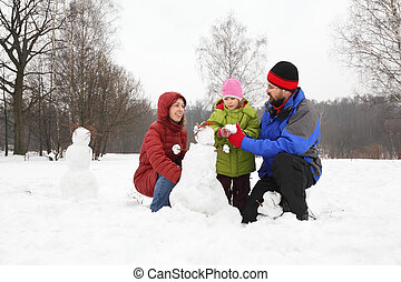 Family from three persons plays in park in winter and sculp...