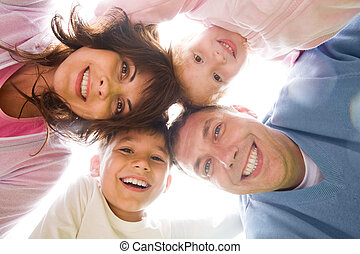 Below view of family members head by head smiling at camera