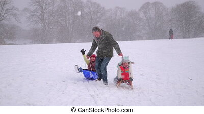 Family Fun in the Snow - Mature man is pulling his daughters...
