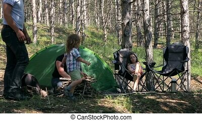 Family fun in the woods with a tent.