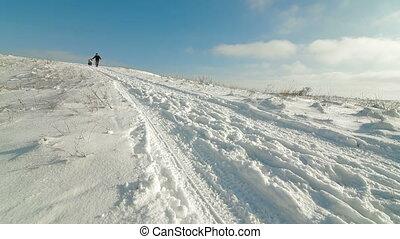 family sledding downhill in winter