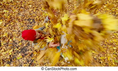 Family Fun - Mother with kids tossing leaves in the air